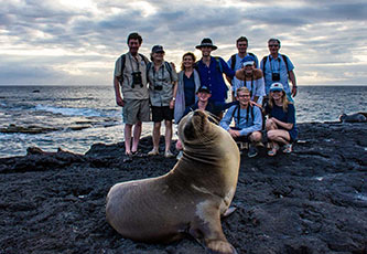 Group of friends posing with a Galapagos Sea Lions