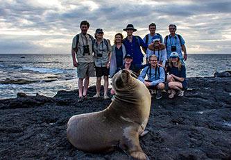 Grupo de amigos posando con un lobo marino de Galápagos