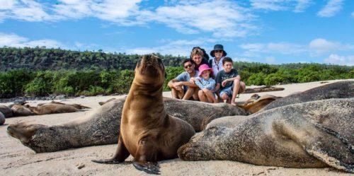 Familia posando con una colonia de lobos marinos en la Isla Santa Fe
