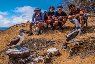 Piquero de patas azules y turistas en Punta Pitt, Galápagos