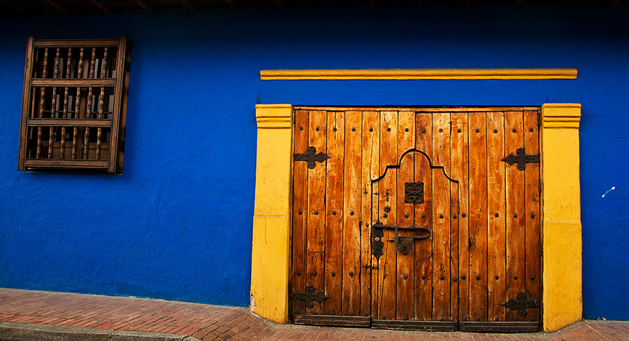 Blue wall and colonial style doors in La Candelaria neighborhood Bogota, Colombia