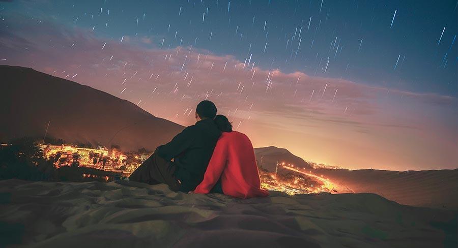 Pareja mirando las estrellas en el desierto de Huacachina, Perú