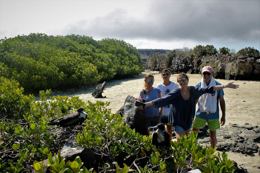 Family poses for a photo next to some frigatebirds in the Galapagos