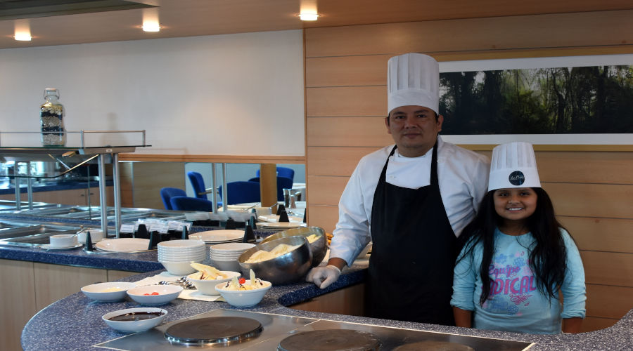 Child visitor stands next to a cruise´s head chef
