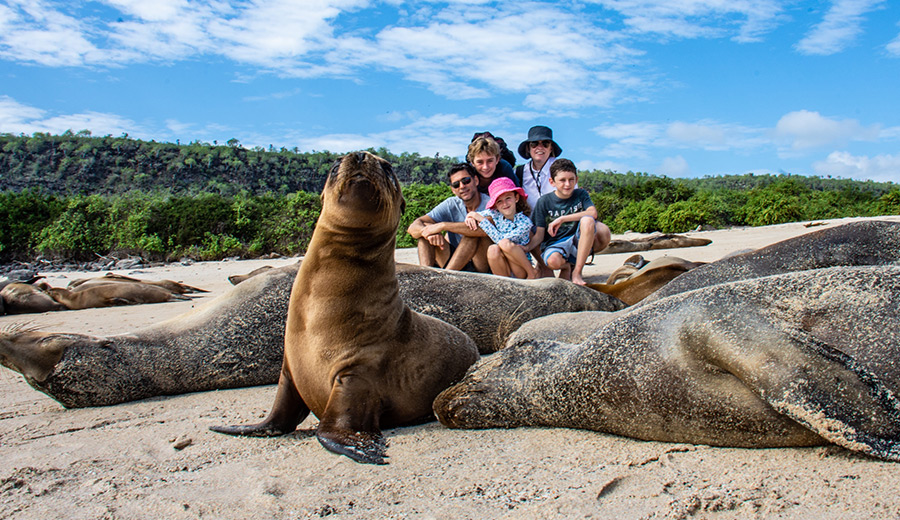 Family posing next to a Galapagos Sea Lion.