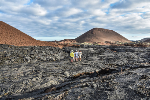 Guests walking on lava fields in Galapagos.