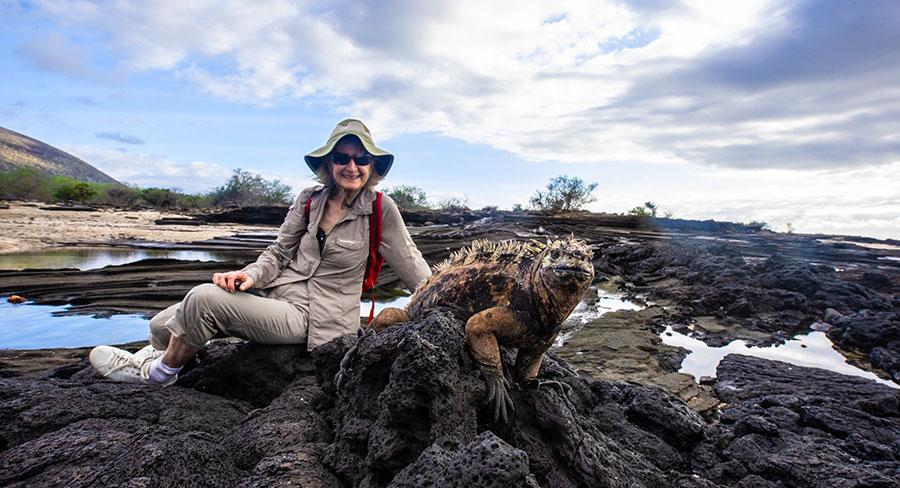 Senior Traveler posing with a Galapagos land Iguana in Santiago Island