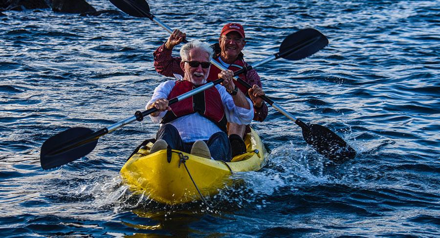 Senior travelers kayaking in Gardner Bay, Galapagos