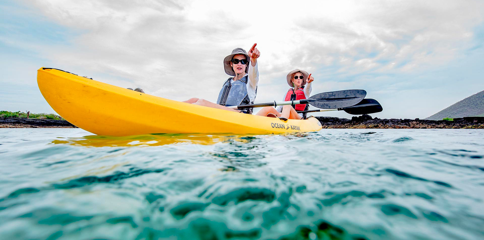 Couple of women kayaking and admiring the view in Galapagos