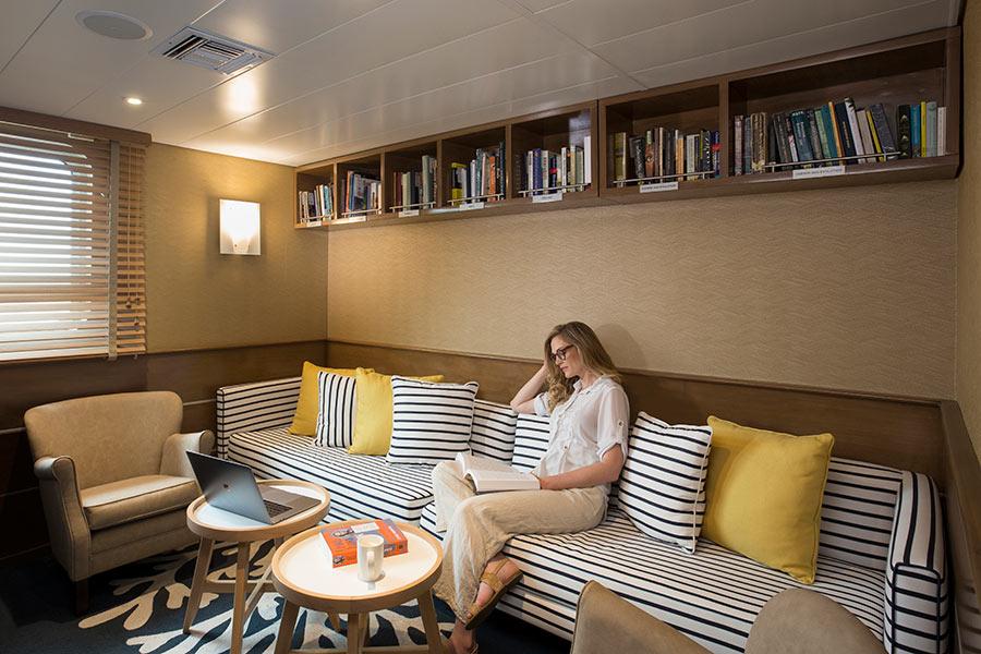 Woman reading alone aboard Yacht La Pinta in the Galapagos Islands, Ecuador
