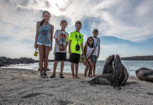 Children meet sea lions in Santa Fe Island